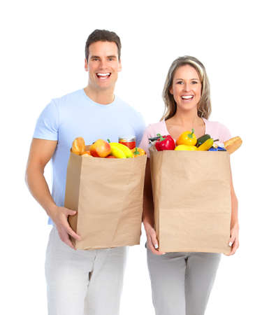Happy young couple carrying shopping bags with food  photo