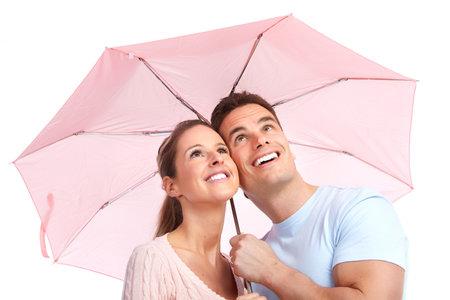 Happy smiling couple under a pink umbrella   Imagens