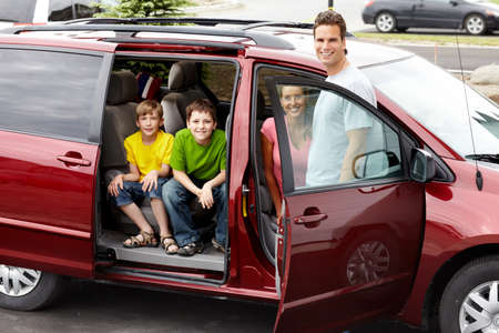 car inside: Smiling happy family and a family car