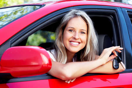 Driving a car: Woman with a car key.