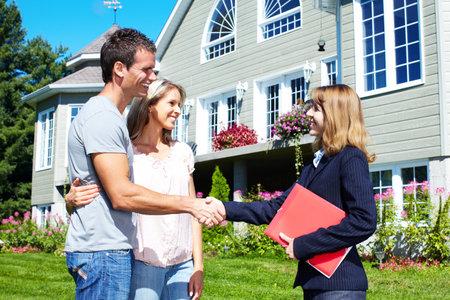 brokers: Happy family near new house.