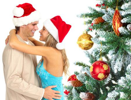 man woman hugging: Happy couple near Christmas Tree.