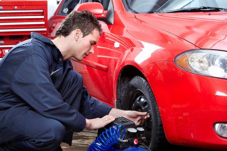 Auto mechanic changing a tire. Stock Photo - 11293342