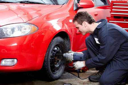 auto repair: Auto mechanic changing a tire.
