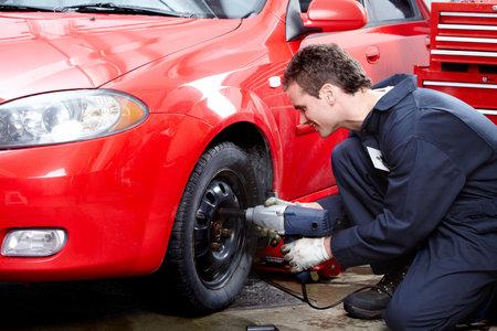 auto shop: Auto mechanic changing a tire.