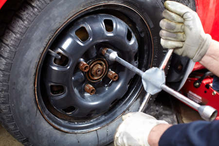 Auto mechanic changing a tire. photo