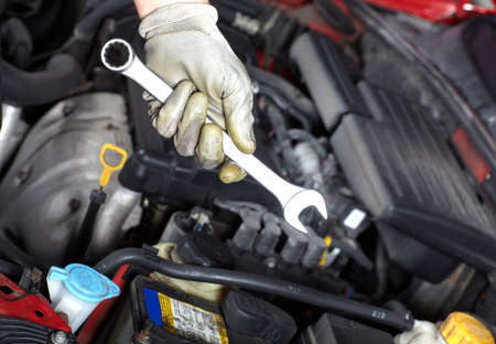 Hand with wrench. Auto mechanic. photo