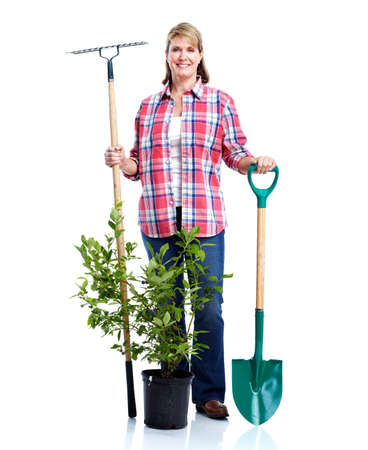 Senior woman with rake and plant. photo
