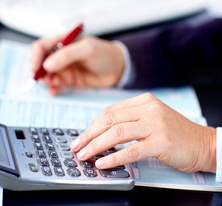 電卓: ビジネスの女性は、ドキュメントでの作業します。