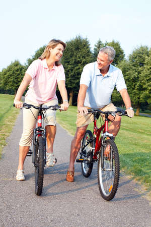 Senior couple cycling in park. photo