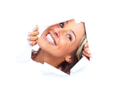 torn: Happy young woman looking through a hole. Stock Photo