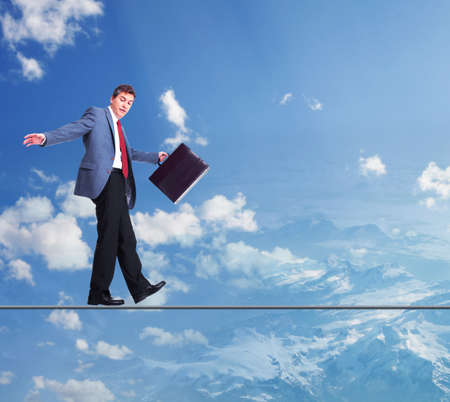 Businessman walking on rope in the sky  photo