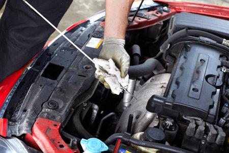 manos sucias: Mecánico de automóviles revisar el aceite