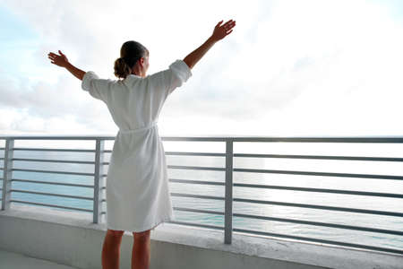 hotel balcony: Happy woman looking on the ocean
