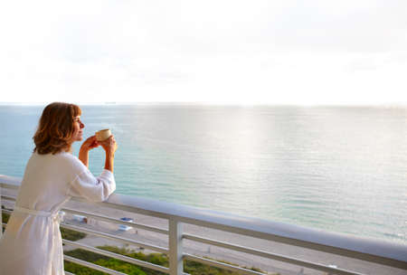 balcony view: Happy woman looking on the ocean