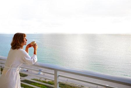 mujer tomando cafe: Mujer feliz que mira en el océano
