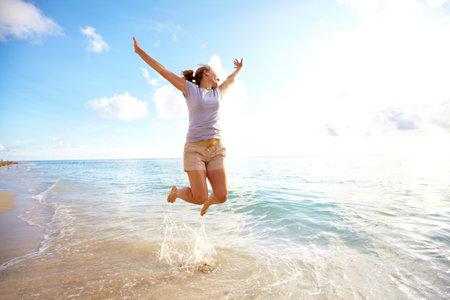 persona saltando: Mujer feliz saltando en la playa