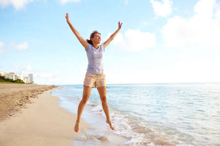 Happy woman jumping on the beach Stock Photo - 15594030