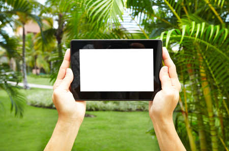 telephony: Hands with tablet computer in tropical garden.  Vacation.
