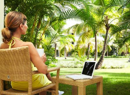 열대 정원에서 노트북 컴퓨터와 여자입니다. 휴가.