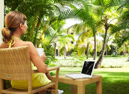 tablet: Woman with laptop computer in the tropical garden. Vacation.