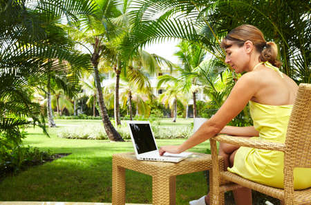 luxuries: Woman with laptop computer in the tropical garden. Vacation.