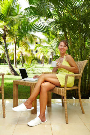 Woman with laptop computer in the tropical garden. Vacation. photo