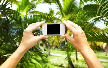 ecran: Woman with a smartphone in tropical garden. Vacation.