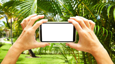 Woman with a smartphone in tropical garden. Vacation. Stock Photo - 16080653