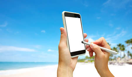 Hand with a smartphone. Exotic tropical vacation.