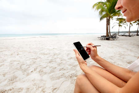 tablet: Woman with a smartphone on the beach. Vacation.