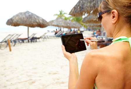 Woman with a smartphone on the beach. Vacation. photo