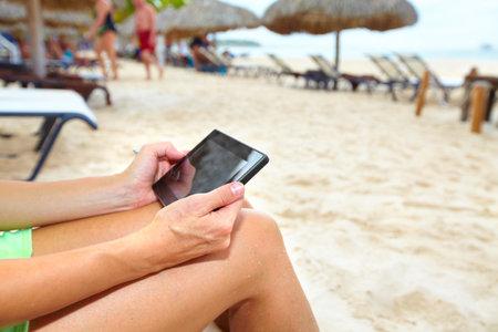 fiestas electronicas: Mujer con un tel�fono inteligente en la playa. Vacaciones.