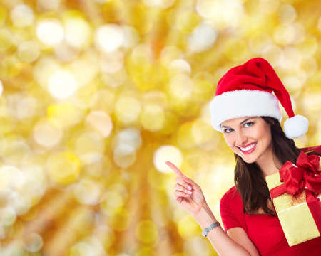 Beautiful happy Christmas Santa woman with gift  Over sparkle background  photo