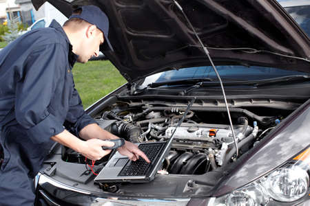 Car mechanic working in auto repair service  photo