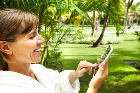 Woman with a smartphone in tropical garden. Vacation. photo
