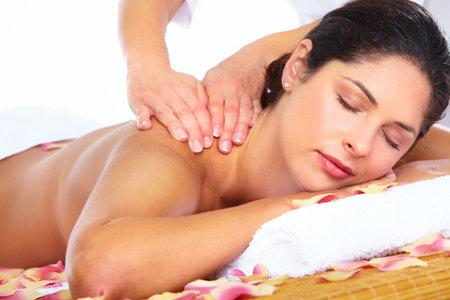 mimos: Mujer hermosa joven que consigue masaje en el salón de spa.