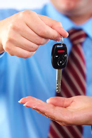 Hand with a car key. Isolated on white background. photo