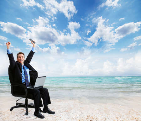 Businessman with laptop on the beach photo