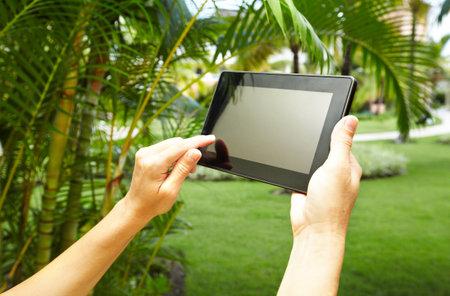 Hands with tablet computer in tropical garden