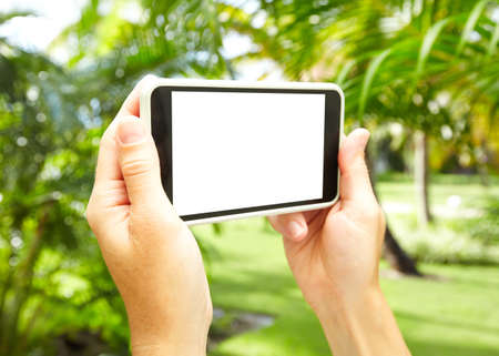 Woman with a smartphone in tropical garden  photo