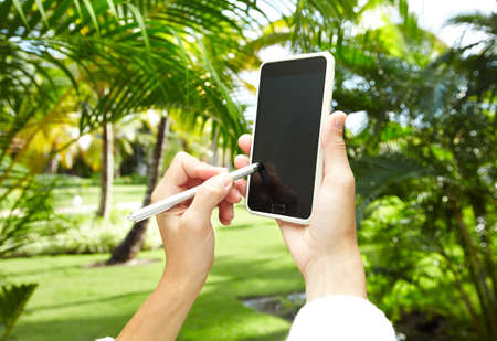 Woman with a smartphone in tropical garden