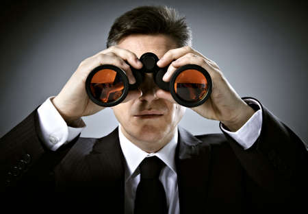 Businessman with binoculars  photo