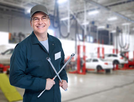car workshop: Auto mechanic with a wheel wrench  Stock Photo