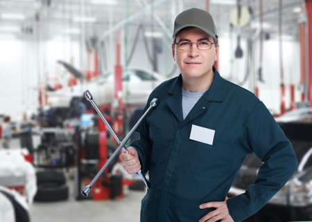 automobile workshop: Auto mechanic with a wheel wrench  Stock Photo