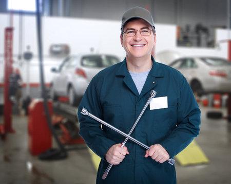 automotive technician: Auto mechanic with a wheel wrench  Stock Photo