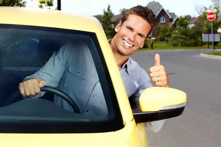 Gelukkig jonge man bestuurder in een nieuwe auto.