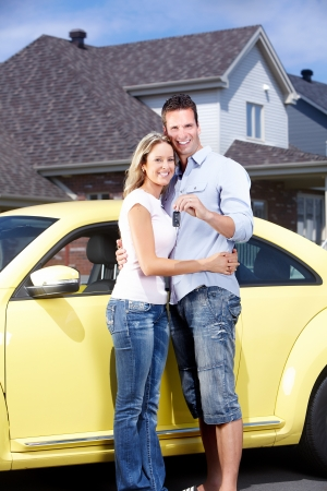Happy young couple near new car with a key. Reklamní fotografie