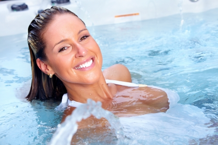 Happy woman relaxing in hot tub. Vacation.