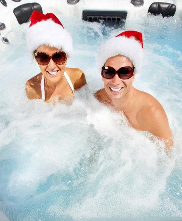 Happy christmas santa couple in hot tub. Vacation.